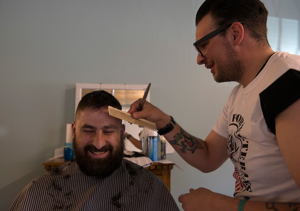""". DENVER, CO - APRIL 25: Donating his time, Riley Bigelow, right, gives Army veteran Thomas Barta a cut and beard trim. Volunteers of America along with other organizations, hosts a \""""Haircuts for Veterans\"""" event at the Bill Daniels Veteran Service Center in Denver on Monday, April 25, 2016. Along with the haircuts, veterans have access to housing service assistance, assistance with job and education opportunities, as well as a hot meal. (Photo by Kathryn Scott Osler/The Denver Post)"""