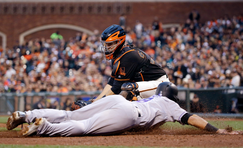 . Colorado Rockies\' Gerardo Parra, bottom, scores on a fielder\'s choice past the tag attempt from San Francisco Giants catcher Buster Posey during the second inning of a baseball game Friday, May 6, 2016, in San Francisco. (AP Photo/Marcio Jose Sanchez)