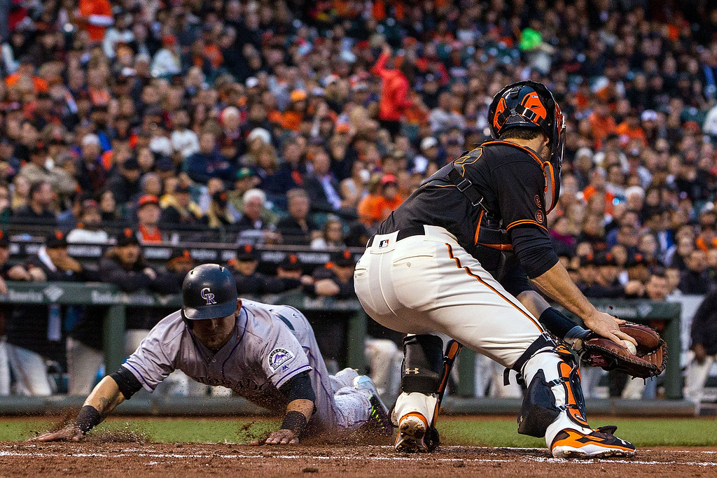 . SAN FRANCISCO, CA - MAY 06: Gerardo Parra #8 of the Colorado Rockies dives into home plate to score a run ahead of a tag from Buster Posey #28 of the San Francisco Giants during the second inning at AT&T Park on May 6, 2016 in San Francisco, California.  (Photo by Jason O. Watson/Getty Images)
