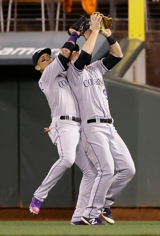 . Colorado Rockies second baseman DJ LeMahieu, right, collides with right fielder Carlos Gonzalez, left, as LeMahieu makes a catch on a pop fly from San Francisco Giants\' Joe Panik during the fifth inning of a baseball game Friday, May 6, 2016, in San Francisco. (AP Photo/Marcio Jose Sanchez)