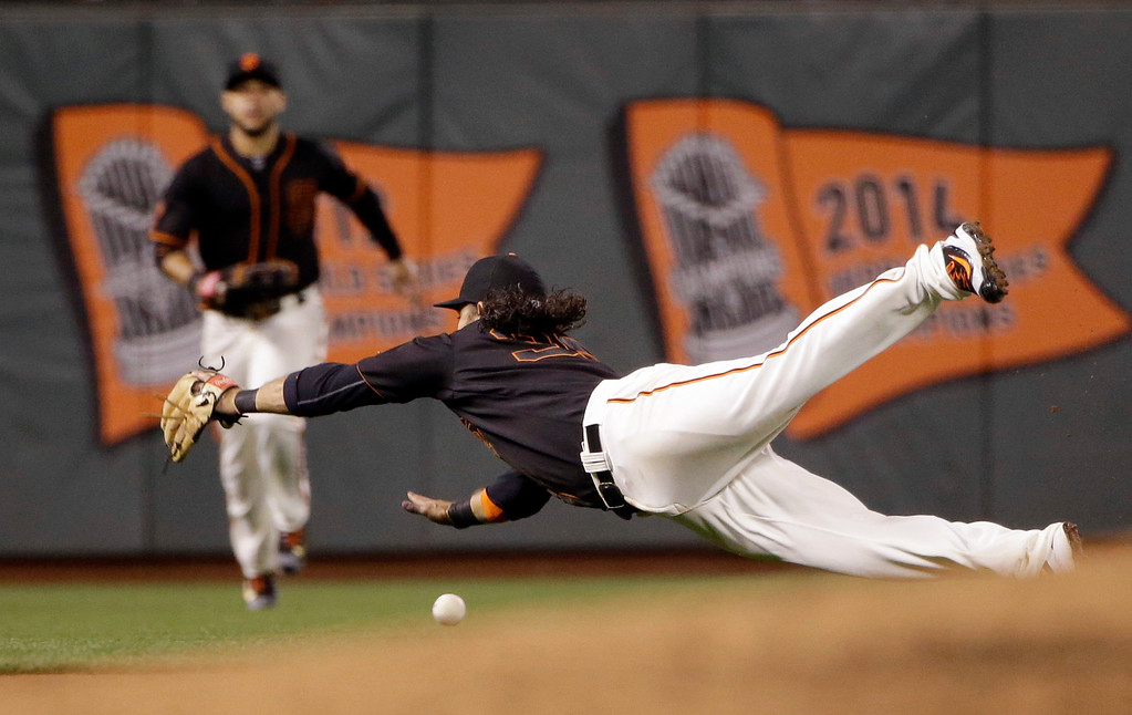 . San Francisco Giants shortstop Brandon Crawford dives but can\'t catch a fly ball from Colorado Rockies\' Mark Reynolds during the sixth inning of a baseball game Friday, May 6, 2016, in San Francisco. (AP Photo/Marcio Jose Sanchez)