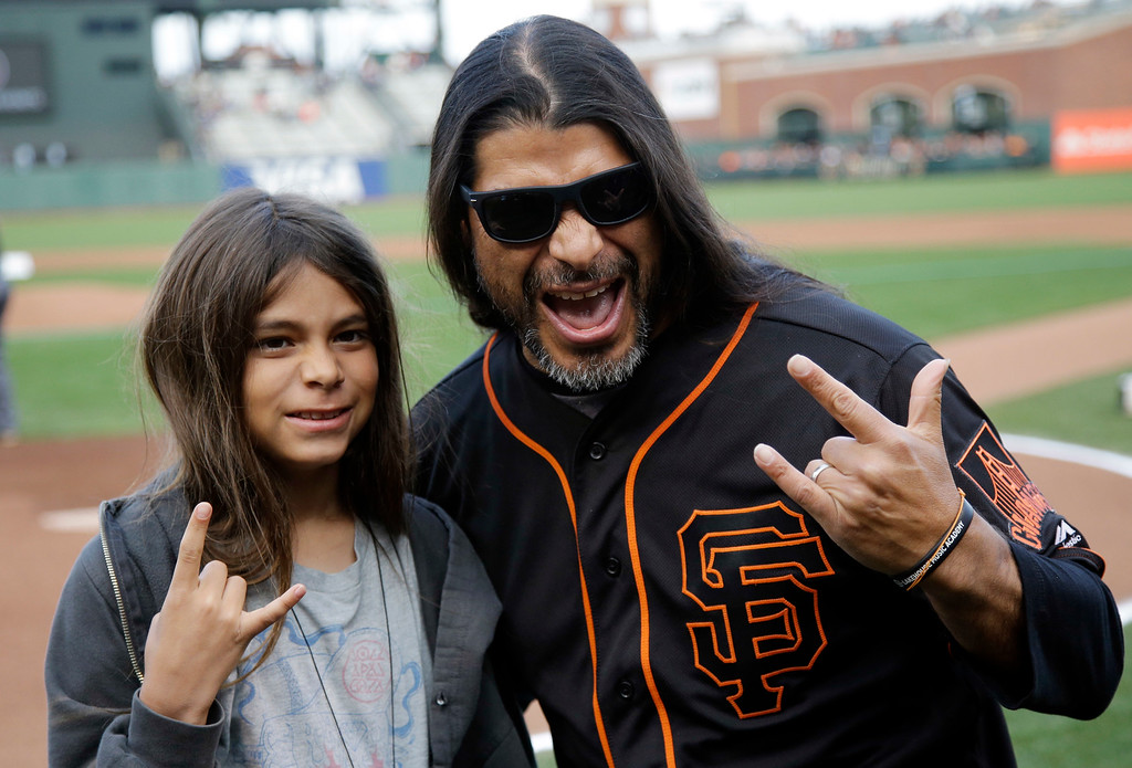 . Metallica\'s Robert Trujillo, right, poses for pictures with his son Tye before a baseball game between the San Francisco Giants and Colorado Rockies Friday, May 6, 2016, in San Francisco. (AP Photo/Marcio Jose Sanchez)