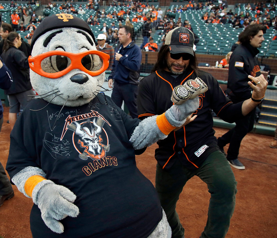 . Metallica\'s Robert Trujillo, right, plays air guitar with mascot Lou Seal before a baseball game between the San Francisco Giants and Colorado Rockies Friday, May 6, 2016, in San Francisco. (AP Photo/Marcio Jose Sanchez)