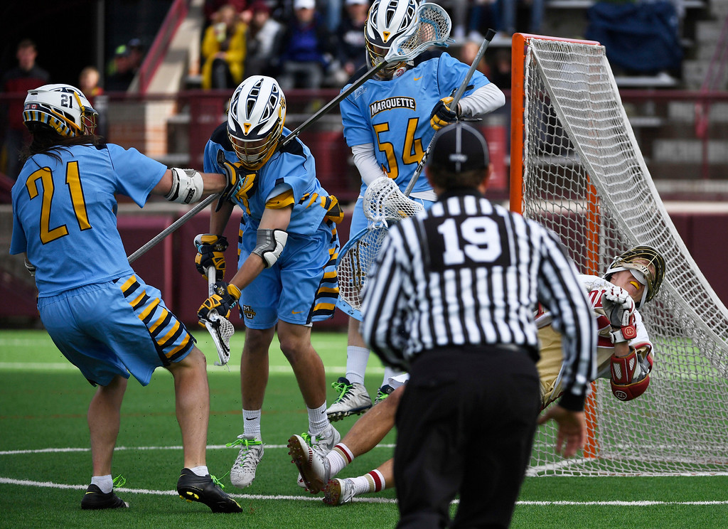 . Denver Pioneers Jack Bobzien #11 gets hit going after a loose ball against Marquette Golden Eagles Liam Byrnes #21, Griffin Connor #3 and Marquette goalie Cole Blazer #54 in the fourth quarter during the Big East Championship game at Peter Barton Stadium May 07, 2016. (Photo by Andy Cross/The Denver Post)