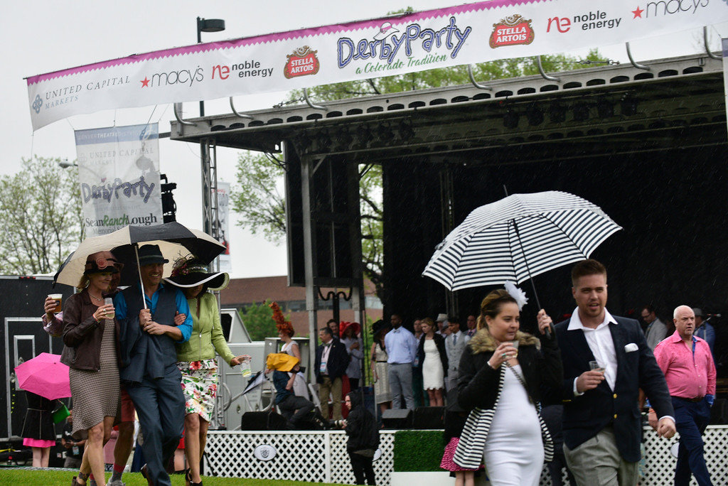 . Partygoers head for shelter as rain falls during the Denver Derby Party at the Performing Arts Complex in Denver, Colorado, Saturday, May 7, 2016. The event featured The Macy\'s Best Hat Contest, and also awarded 3 full ride scholarships to students heading to Colorado State University. (Brenden Neville/Special to the Denver Post)