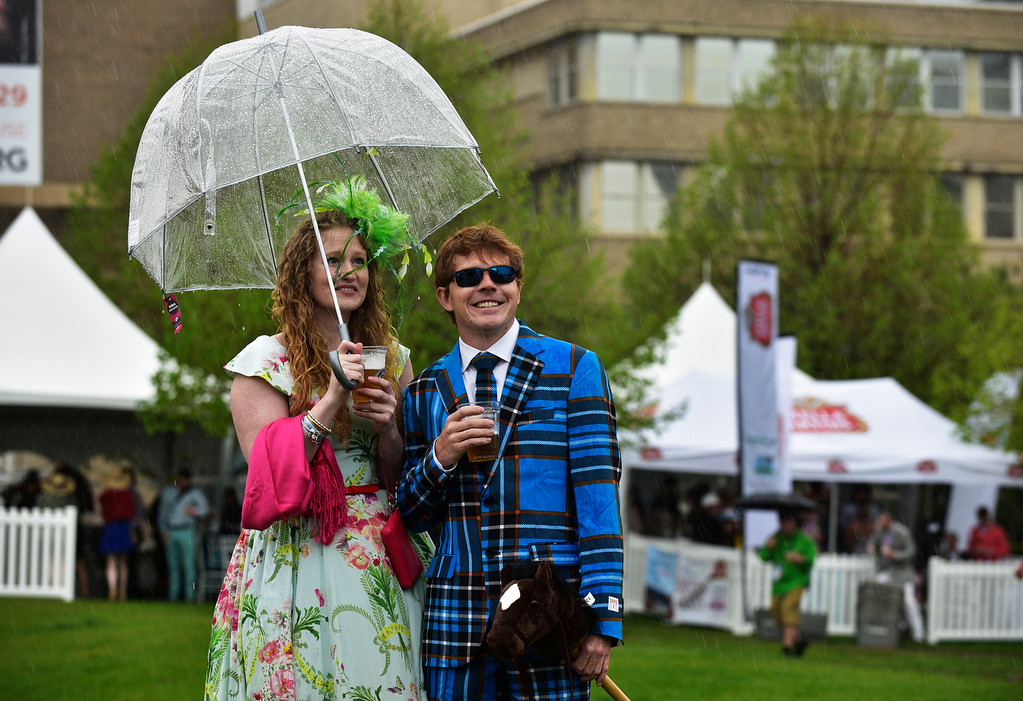 . Jennifer Peck and Andy Scherm stand together in a rain shower during the Denver Derby Party at the Performing Arts Complex in Denver, Colorado, Saturday, May 7, 2016. The event featured The Macy\'s Best Hat Contest, and also awarded 3 full ride scholarships to students heading to Colorado State University. (Brenden Neville/Special to the Denver Post)