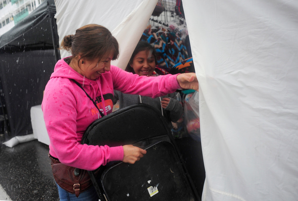 . Carolina Sican (left) rushes into her Guatemala Imports tent with her daughter Jessica Sican (right) as hail falls during the 29th Annual Cinco De Mayo Celebration at Civic Center Park in downtown Denver, Colorado, Saturday, May 7, 2016. Festivities were hampered by afternoon showers and some hail on Saturday, however festivities will continue on Sunday. (Brenden Neville/Special to the Denver Post)