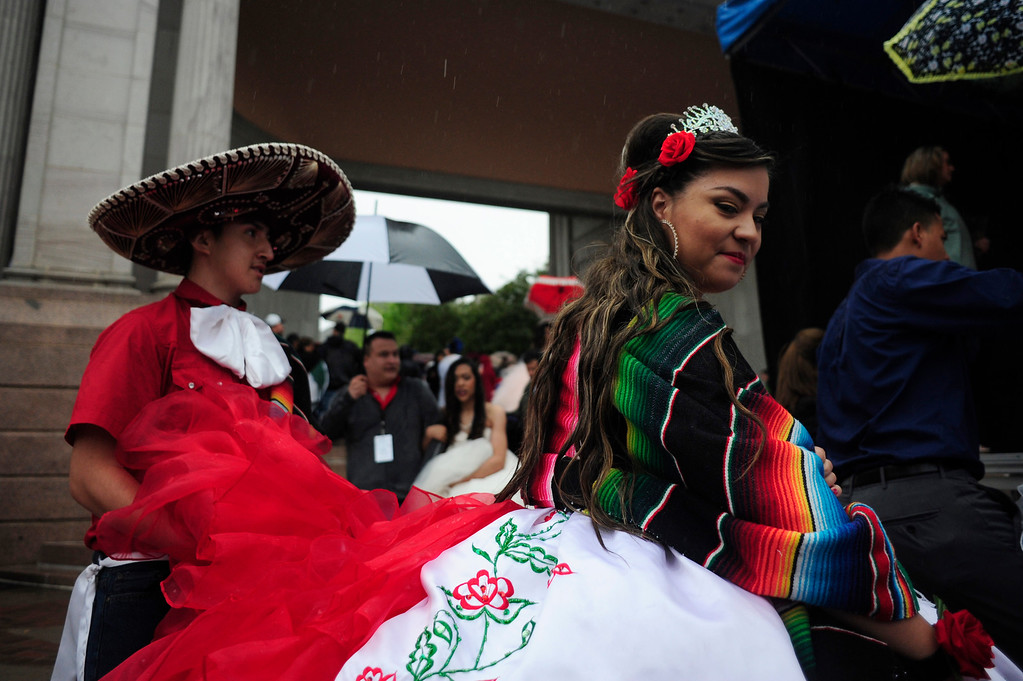 . Katia Ponce De Leon (right) walks towards the stage during the Quinceanera Fashion Show, with Luis Ramirez holding up her dress at right, during the 29th Annual Cinco De Mayo Celebration at Civic Center Park in downtown Denver, Colorado, Saturday, May 7, 2016. Festivities were hampered by afternoon showers and some hail on Saturday, however festivities will continue on Sunday. (Brenden Neville/Special to the Denver Post)