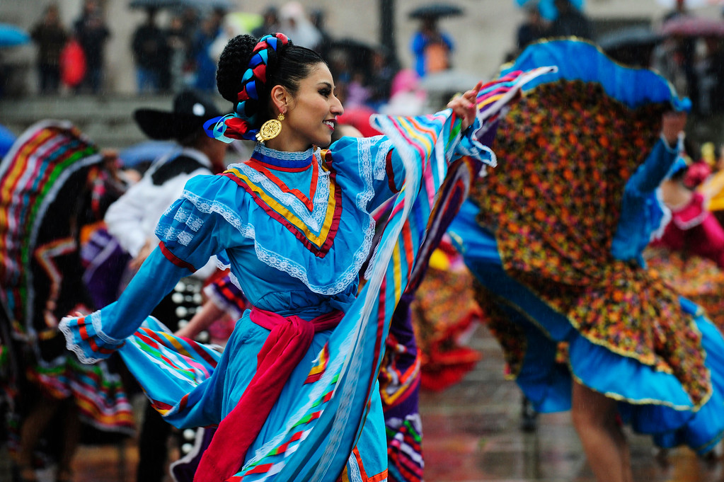 . A dancer performs in the rain during the 29th Annual Cinco De Mayo Celebration at Civic Center Park in downtown Denver, Colorado, Saturday, May 7, 2016. Festivities were hampered by afternoon showers and some hail on Saturday, however festivities will continue on Sunday. (Brenden Neville/Special to the Denver Post)