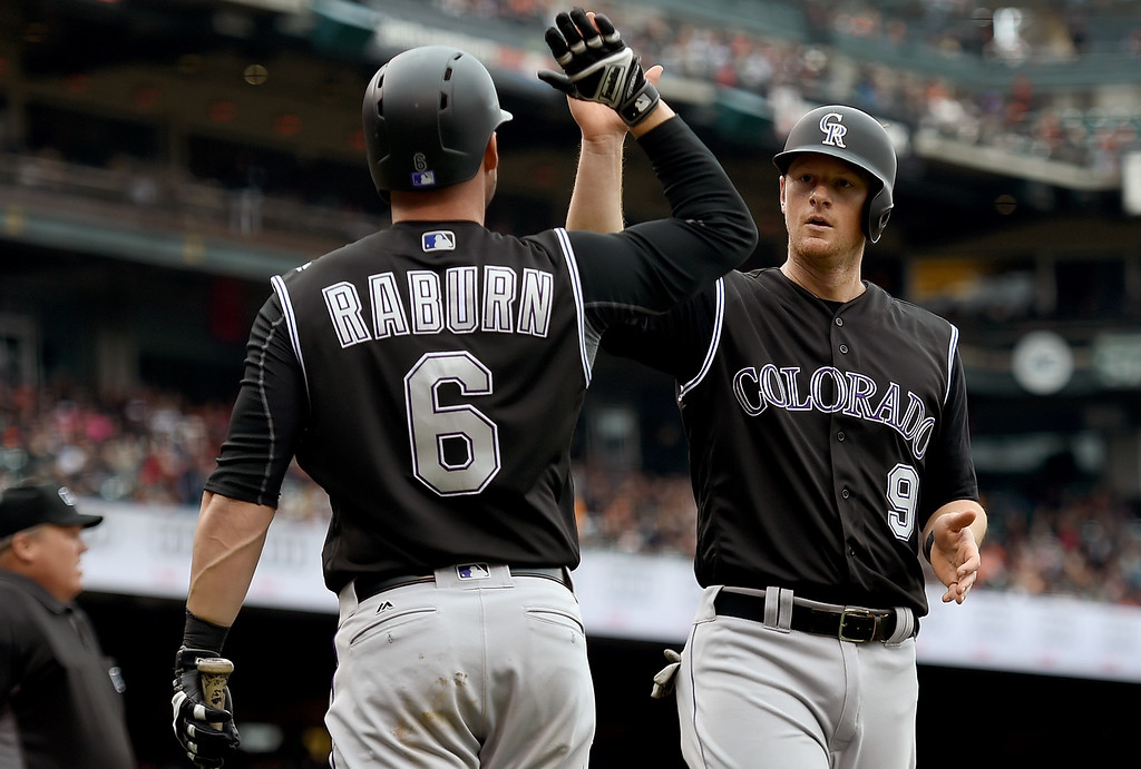 . SAN FRANCISCO, CA - MAY 07:  DJ LeMahieu #9 of the Colorado Rockies is congratulated by Ryan Raburn #6 after LeMahieu scored against the San Francisco Giants in the top of the tenth inning at AT&T Park on May 7, 2016 in San Francisco, California.  (Photo by Thearon W. Henderson/Getty Images)