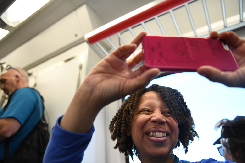 . Natasha Mitchell smile as she take a photo during her ride on the new University of Colorado A-Line from Union Station to Denver International Airport, April 22, 2016. The line is 23 miles with 8 stations along the way. (Photo by RJ Sangosti/The Denver Post)