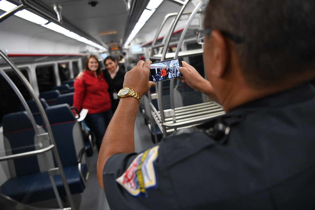 . DENVER, CO - APRIL 22: Tony Vargas, from RTD security, takes a photo of RTD employees on the University of Colorado A-Line that will take commuters from Union Station to Denver International Airport, April 22, 2016. The line is 23 miles with 8 stations. (Photo by RJ Sangosti/The Denver Post)