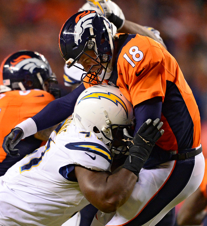 . San Diego Chargers defensive end Damion Square (71) puts a big hit on Denver Broncos quarterback Peyton Manning (18) during the fourth quarter January 3, 2016 at Sports Authority Field at Mile High Stadium. (Photo By Eric Lutzens/The Denver Post)