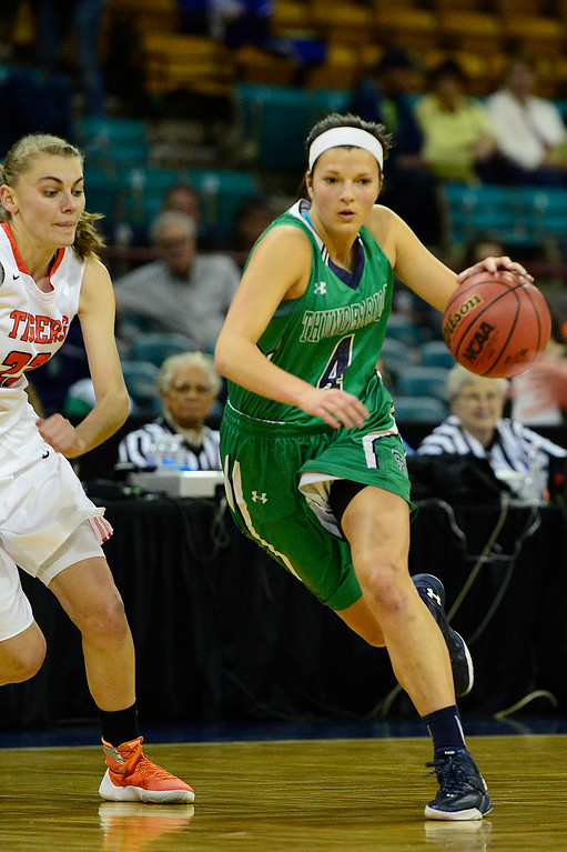 . ThunderRidge scoring guard Taylor Rusk (4) makes her way to the hoop while ThunderRidge power forward Mallory Elson (22) tries to defend during the second quarter at the Denver Coliseum on March 4, 2016 in Denver, Colorado. ThunderRidge took on Lakewood in the quarterfinals of girls 5A basketball tournament. (Photo by Brent Lewis/The Denver Post)