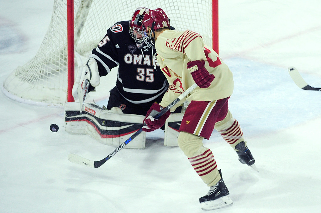 . Denver Pioneers forward Matt Marcinew (23) looks for a shot on Nebraska-Omaha Mavericks goalie Evan Weninger (35) during the third period at Magness Arena on March 4, 2016 in Denver, Colorado. Denver defeated Nebraska-Omaha 3-0. (Photo by Brent Lewis/The Denver Post)