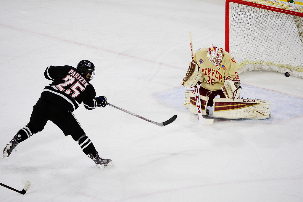 . DENVER, CO - MARCH 4:Nebraska-Omaha Mavericks forward Justin Parizek (25) takes a shot on goal while Denver Pioneers goalie Tanner Jaillet (36) defends during the first period at Magness Arena on March 4, 2016 in Denver, Colorado. (Photo by Brent Lewis/The Denver Post)