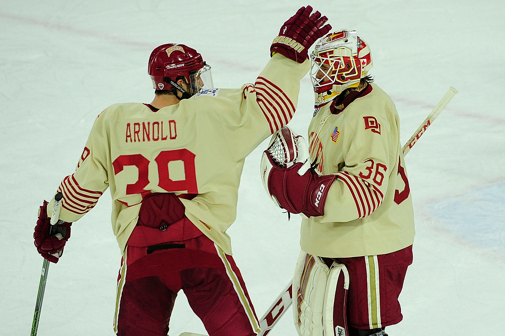 . Forward Grant Arnold (39) pats Denver Pioneers goalie Tanner Jaillet (36) on the head at end of the game at Magness Arena on March 4, 2016 in Denver, Colorado. Denver defeated Nebraska-Omaha 3-0. (Photo by Brent Lewis/The Denver Post)