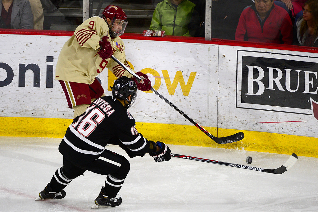 . Denver Pioneers forward Gabe Levin (9) gets the puck around the defense of Nebraska-Omaha Mavericks forward Austin Ortega (16) during the first period at Magness Arena on March 4, 2016 in Denver, Colorado. (Photo by Brent Lewis/The Denver Post)