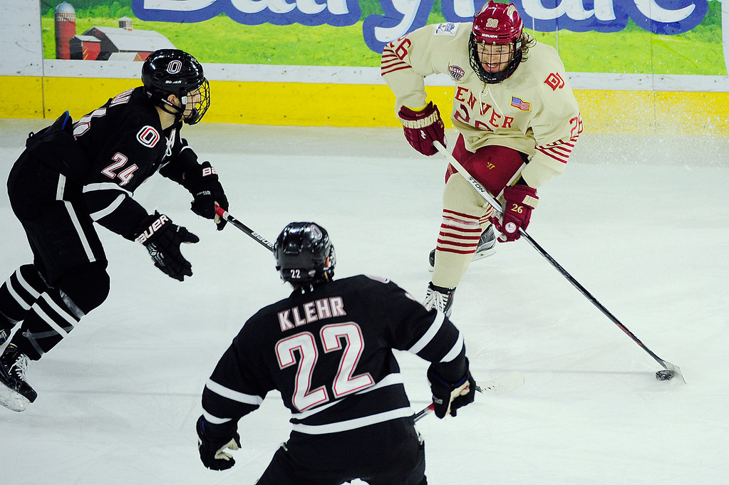 . Denver Pioneers forward Evan Janssen (26) looks for a way around defenseman Ian Brady (24) and Nebraska-Omaha Mavericks defenseman Jordan Klehr (22) during the third period at Magness Arena on March 4, 2016 in Denver, Colorado. Denver defeated Nebraska-Omaha 3-0. (Photo by Brent Lewis/The Denver Post)