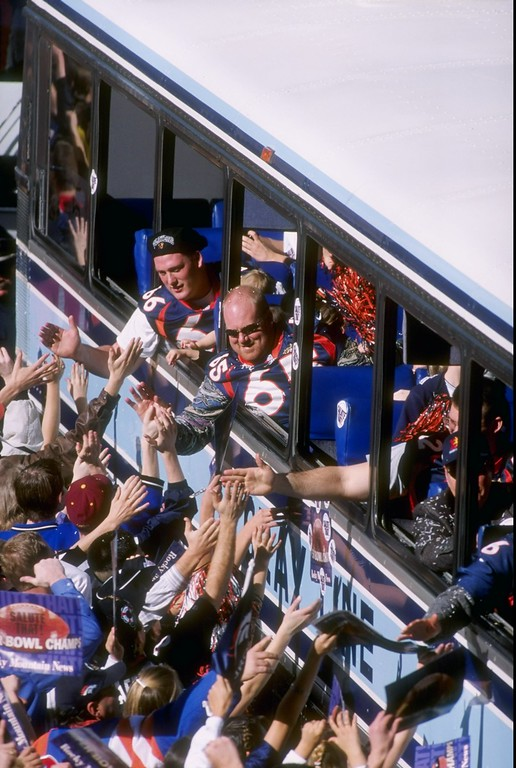 . Tom Nalen #66 and Gary Zimmerman #65 of the Denver Broncos celebrate while hanging out of a bus during the Broncos Super Bowl XXXII victory parade in Denver Colorado in 1998. The Broncos defeated the Green Bay Packers 31-24 in Super Bowl XXXII. (Photo by Nevin Reid/Getty Images)