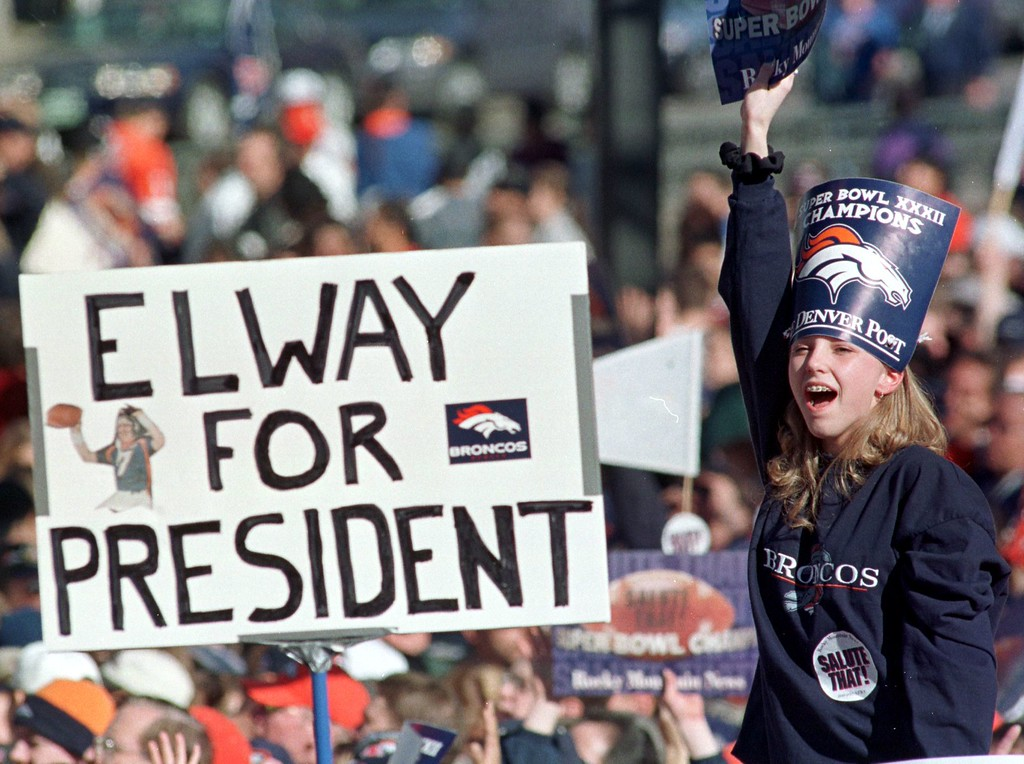 ". A fan cheers in front of a sign reading ""Elway for President\"" during a rally and parade held in honor of Super Bowl Champion Denver Broncos January 27, 1998 at the City and County Building in Downtown Denver, Colorado. Several thousand people watched and cheered the Broncos in the rally for their Super Bowl XXXII victory over the Green Bay Packers. DOUG COLLIER/AFP/Getty Images"