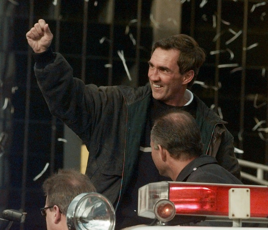 . Denver Broncos head coach Mike Shanahan waves to the cheers of fans as he rides on top of a fire truck during a victory parade in  downtown Denver on Monday, Feb. 1, 1999. The Broncos returned to Denver Monday after winning Super Bowl XXXIII to the cheers of over 350,000 fans.  (AP Photo/Ed Andrieski)