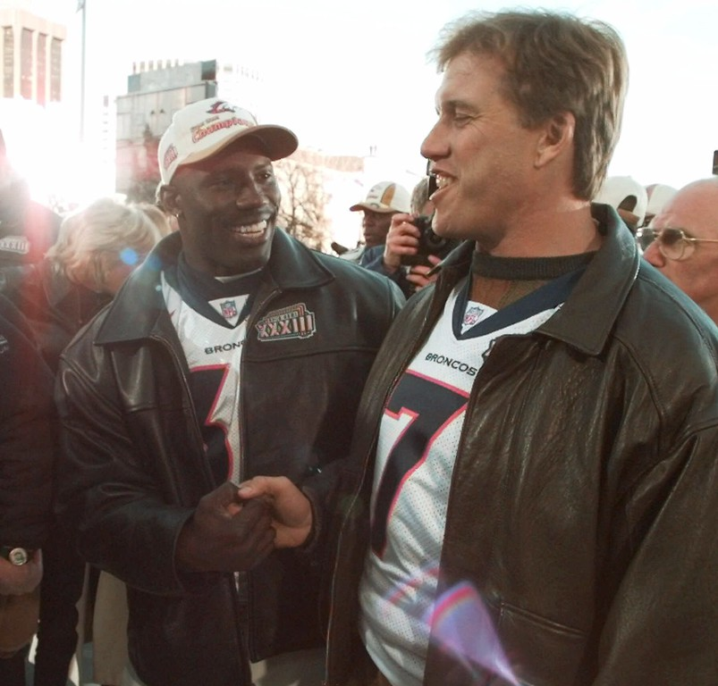 . Denver Broncos running back Terrell Davis, left, and quarterback John Elway share a laugh and a hand shake after a victory rally in  downtown Denver on Monday, Feb. 1, 1999. The Broncos returned to Denver Monday after winning Super Bowl XXXIII to the cheers of over 350,000 fans.  (AP Photo/Ed Andrieski)