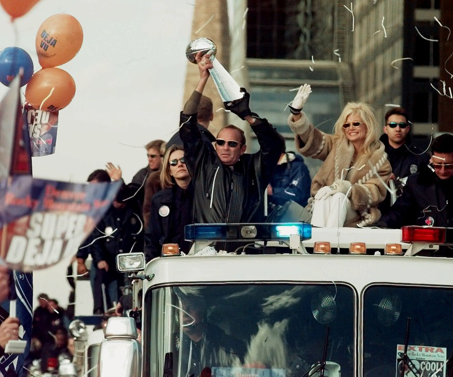 . Denver Broncos owner Pat Bowlen holds the Vince Lombardi Super Bowl trophy over his head and his wife, Annabel, right, waves, as they ride a fire truck through downtown Denver in a victory parade on Monday, Feb. 1, 1999. The Broncos returned to Denver Monday after winning Super Bowl XXXIII. (AP Photo/Ed Andrieski)