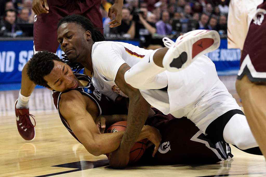 . DENVER, CO - MARCH 19: Mareik Isom (14) of the Arkansas Little Rock Trojans and Jameel McKay (1) of the Iowa State Cyclones dive for a loose ball during the second half of Iowa State\'s 78-61 second round NCAA Tournament game win on Saturday, March 19, 2016. (Photo by AAron Ontiveroz/The Denver Post)
