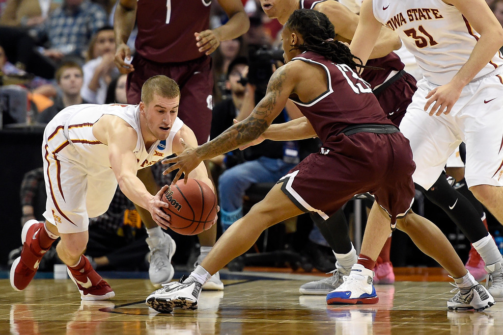 . DENVER, CO - MARCH 19: Matt Thomas (21) of the Iowa State Cyclones dives for a loose ball against Marcus Johnson Jr. (13) of the Arkansas Little Rock Trojans during the second half of Iowa State\'s 78-61 second round NCAA Tournament game win on Saturday, March 19, 2016. (Photo by AAron Ontiveroz/The Denver Post)
