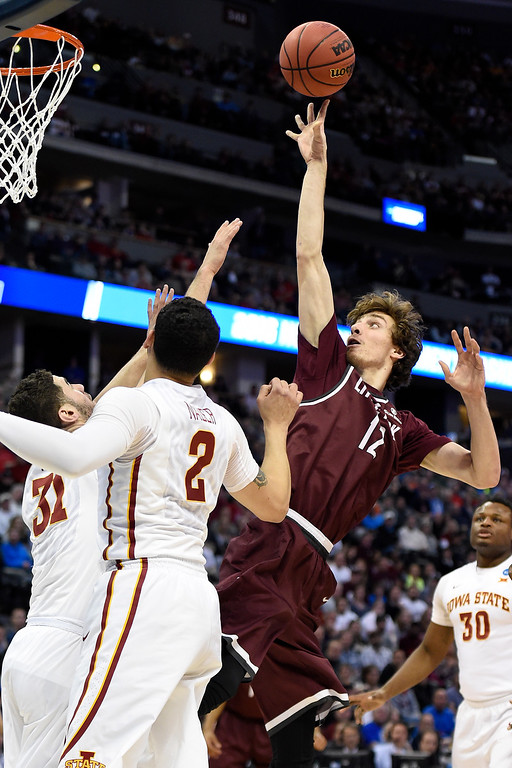 . DENVER, CO - MARCH 19: Lis Shoshi (12) of the Arkansas Little Rock Trojans shoots over Georges Niang (31) of the Iowa State Cyclones and Abdel Nader (2) during the first half of their second round NCAA Tournament game on Saturday, March 19, 2016. (Photo by AAron Ontiveroz/The Denver Post)