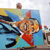 (AC) DENVER, CO--AUGUST 23rd 2008--Ron Benson, marketing director for Denver artist Malcolm Farley, carries an unfinished painting of Barack Obama, to a location in front of the Farris wheel at Elithes Saturday evening, just before the DNC Media party at Elitch Gardens. THE DENVER POST/ANDY CROSS