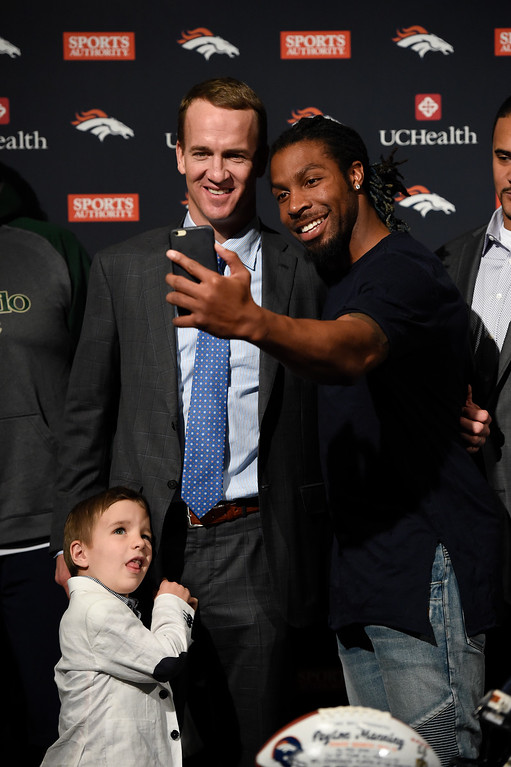 . ENGLEWOOD, CO - MARCH 07: Peyton Manning takes a selfie with David Bruton as Manning\'s son Marshall stands below after his press conference. The Denver Broncos hold a press conference to announce the retirement of Denver Broncos quarterback Peyton Manning March 7, 2016 at UCHealth Training Center. (Photo By John Leyba/The Denver Post)