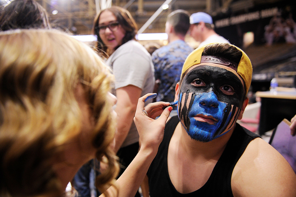 . Daniel Hernandez gets his face painted by Kayla West before the start of the Pueblo West and Vista Ridge game at the Coors Events Center on March 11, 2016 in Boulder, Colorado. (Photo by Brent Lewis/The Denver Post)