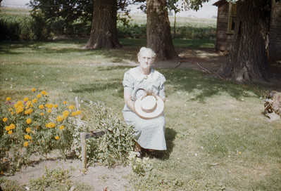 Grandma Baadsgaard, in front of the trees Foster cut down when he got back from the army.