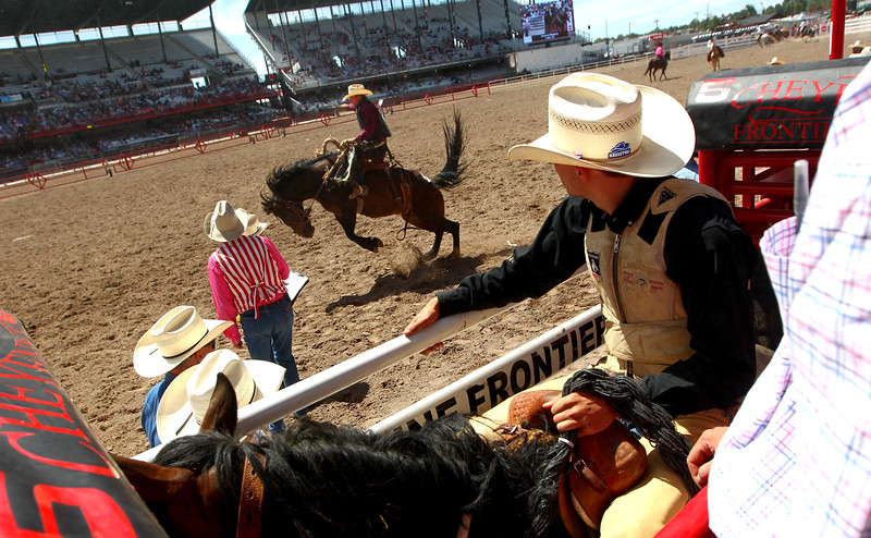 Lane Schuelke, of Newell, SD, watches Chance Masters, of Leon, IA, from his seat in the chute during the rookie bronc competition Thursday, July 25, 2019, at Frontier Park Arena in Cheyenne. Thursday was the sixth rodeo of the 123rd Cheyenne Frontier Days, which continues daily through Sunday's championships. Nadav Soroker/Wyoming Tribune Eagle