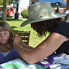 Adriane Huber of Teutopolis patiently allows Megan Hoelscher to paint her face during the Old Settlers Reunion Sept. 27.