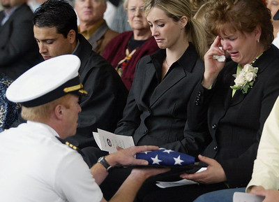 Commander Chris Silver passes the American Flag to Marilyn Cockrell during the memorial for the three fallen pilots in the Aero Union Hanger. - Halley photo 5/4/05
