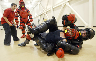 Self-Defense instructor Frankie Hockstaff (far left) and UPD Detective Eric Partika (left) watch Chico Enterprise-Record reporter Melissa Daugherty (middle) swing her arms to free herself from the hold of her attacker as she defends herself from UPD Sgt. Mark Snelgrove during a simulated attack scenario when she took part in a self-defense class offered at Chico State for a first person approach to the story about the class. - halley photo 12/1/05
