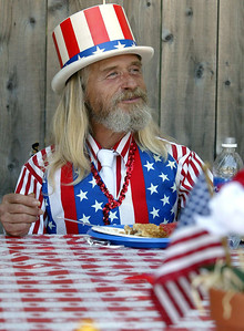 Wayne Owen wore a patriotic outfit as he ate his watermelon and apple pie at the Jesus Center's special Independence Day BBQ for the homeless in Chico at the Jesus Center Parking lot Friday. - halley photo 6/30/06