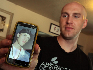 Kevin Baker (right) holds up a cell phone picture of when he was using heroin and about 40lbs lighter as he talks about recovery from heroin use during an interview in their home Friday, August 9, 2013 in Chico, Calif. (Jason Halley/Chico Enterprise-Record)