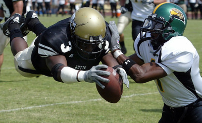 Butte College's #3 David Sims (left) flies the ball into the endzone for a touchdown (7-0) as he is knocked by Feather River College's #1 Ariece Perkins (right) with about 9:40 remaining in the first quarter during thier football game at Cowan Stadium Saturday. - halley photo 9/9/06