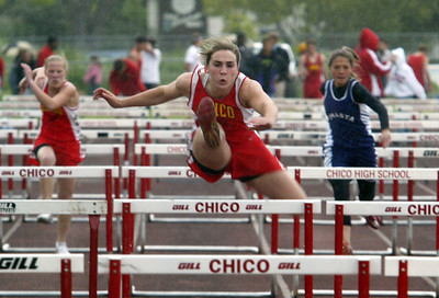 Chico Senior Chelsea Azevedo throws her leg out straight while running the hurdles through a light sprinkle of rain to have a time of 14.44 seconds at the Chico High vs. Shasta Track Meet Tuesday afternoon at the Chico High field.  Azevedo also ran a 12.78 second 100m coming in first.