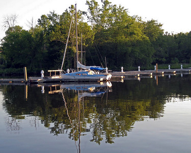 A lone sailboat moored to the dock on the calm evening waters of the Occoquan River