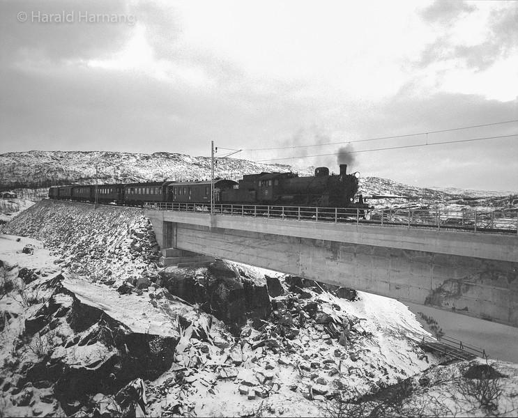 Innlånt svensk B-lok i første tog over nye Norddalsbrua, 1.10.1988. Togturen var sterkt forsinket, lyset nesten borte, og bare få timer for fotograf Harald Harnang til å kjøre hjem, framkalle film, kopiere, ramme inn og levere bildet på festmiddagen.