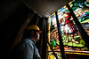 Elijah Zimmer, with the Rockingham historic preservation commission, looks at the stained glass window at 66 Atchison Street, in Bellows Falls, Vt, during a tour of the building by members of the Rockingham Historic Preservation Commission on Monday, Oct. 11, 2021.