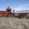 Rusted draper header combine forgotten on a scab rock