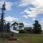 Forgotten farm house and bent up windmill.