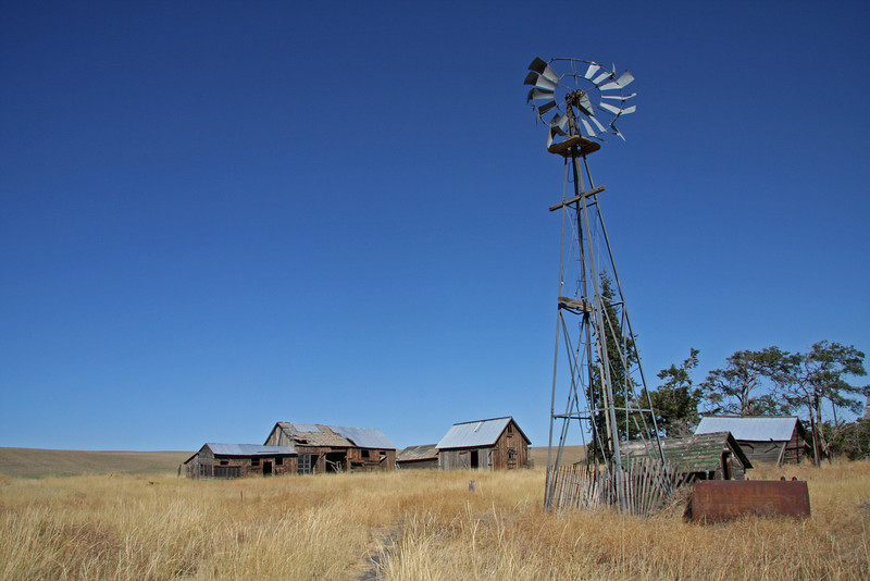 Bent up windmill and weathered outbuildings.