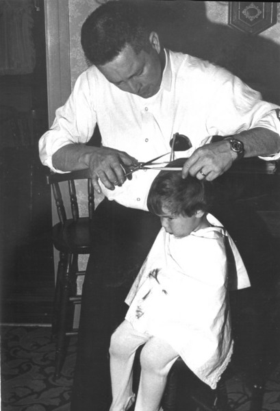 Dick Grady cutting his son T's hair